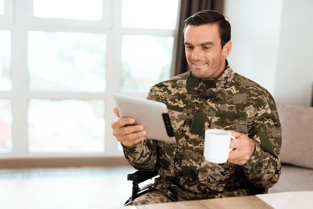 Desativado em uniforme, lendo algo em seu tablet moderno