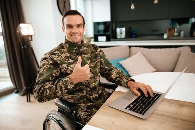 Desativado em uniforme militar, ele se senta ao lado de seu laptop