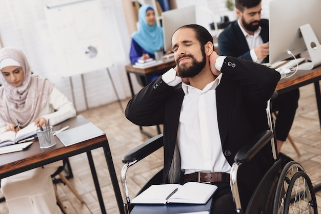 Desativado homem árabe de terno em cadeira de rodas, trabalhando no escritório