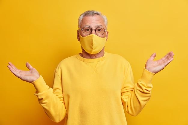 Desavisado homem de cabelos grisalhos não sabe como o que está acontecendo espalha as palmas das mãos e fica confuso contra a parede amarela vívida usa máscara protetora durante a pandemia de coronavírus