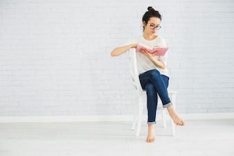Descalço mulher lendo na cadeira
