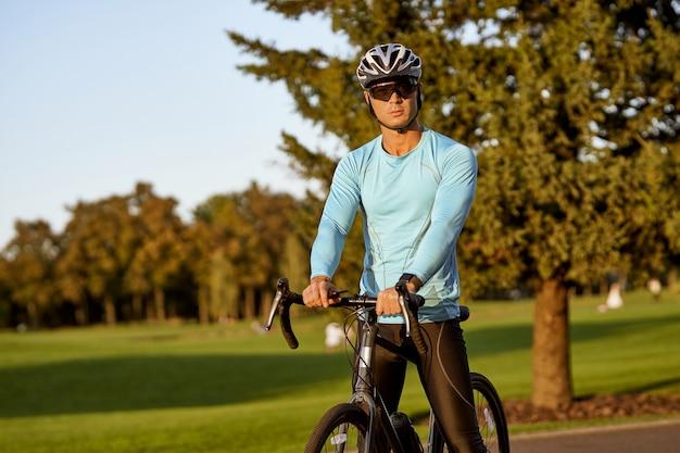 Descansando após um passeio de bicicleta ao ar livre, jovem atlético em roupas esportivas e capacete protetor em pé