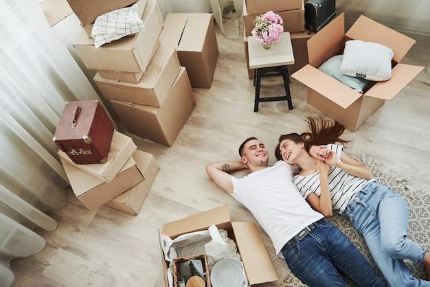 Descansando. deitada no chão. casal jovem alegre em seu novo apartamento. concepção de movimento.