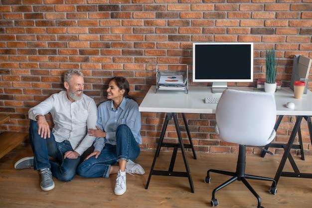 Descansando e conversando. duas pessoas sentadas no chão conversando