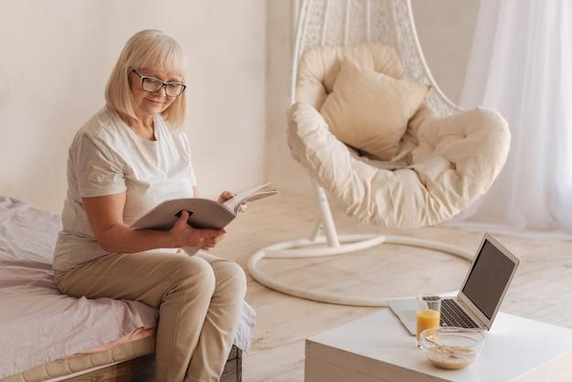 Descansando em casa. mulher idosa, positiva e encantada de óculos e lendo uma revista enquanto descansava em casa