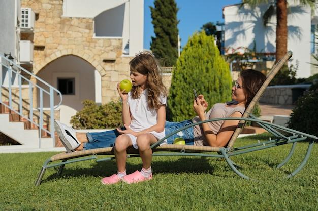Descansando feliz família mãe e filha sentada na cadeira ao ar livre