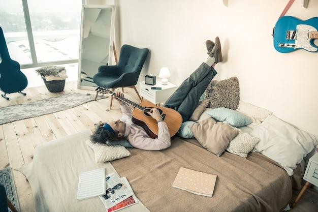 Descansando no quarto. calma cara bonito deitado de cabeça para baixo e colocando as pernas na parede enquanto toca violão