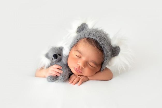 Descansando o recém-nascido em chapeuzinho fofo e com urso de brinquedo cinza nas mãos