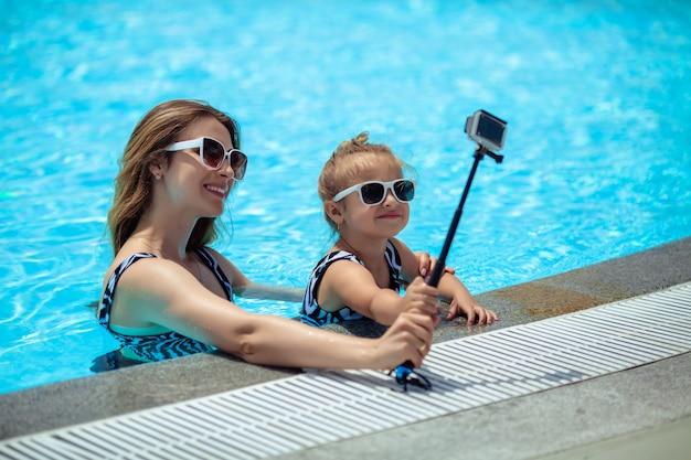 Descanse à beira da piscina no verão no fim de semana. família feliz mãe e filha óculos de sol são fotografados em uma câmera selfie