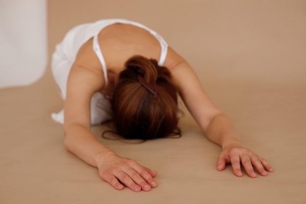 Descanse após um intenso treino de ioga. mulher com roupas brancas sobre fundo bege. dia internacional da ioga