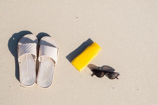 Descanse na praia: chinelos, creme protetor e óculos de sol na areia limpa. vista superior dos acessórios para férias à beira-mar ou férias de verão