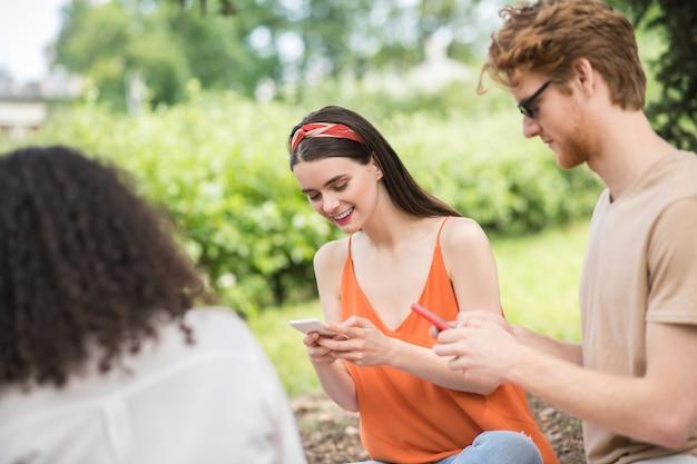 Descanse, natureza. jovens amigos amigáveis olhando atentamente para seus smartphones, descansando na natureza, sentados no chão do parque