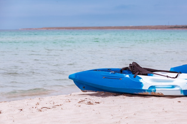 Descanso ativo, esporte, caiaque. barco para rafting na água. alguns caiaques estão em uma praia arenosa.