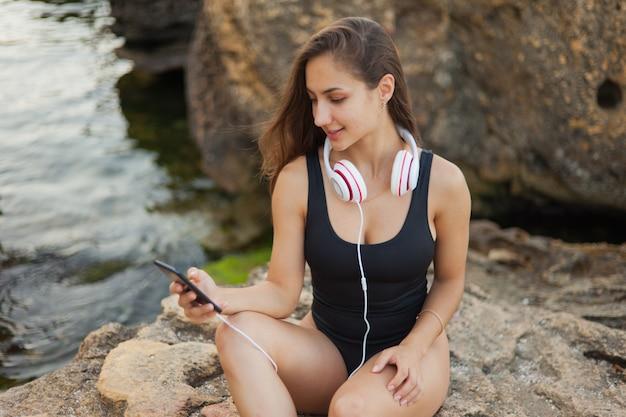 Descanso de verão. jovem mulher sexy de biquíni ouve música com fones de ouvido em uma praia selvagem com pedras