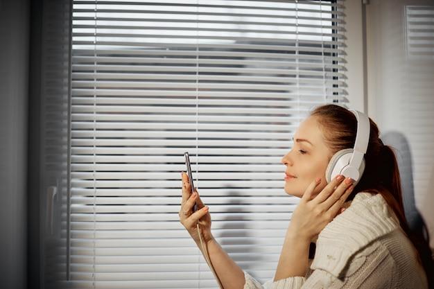 Descanso e relaxamento, jovem mulher caucasiana ouvindo música em fones de ouvido usando um smartphone