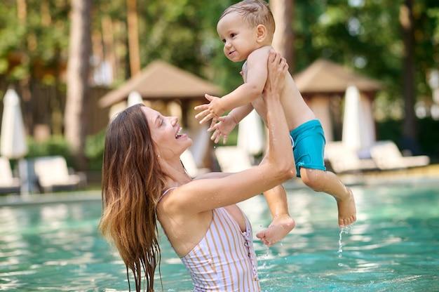 Descanso. uma jovem mulher segurando seu filho e se sentindo bem enquanto nadava em uma piscina