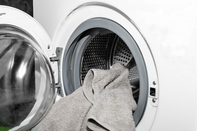 Descarregando a roupa da máquina de lavar. carregando roupas em uma máquina de lavar
