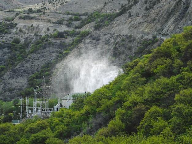Descarte de água em usinas hidrelétricas. usina hidrelétrica nas montanhas cobertas por uma floresta verdejante.