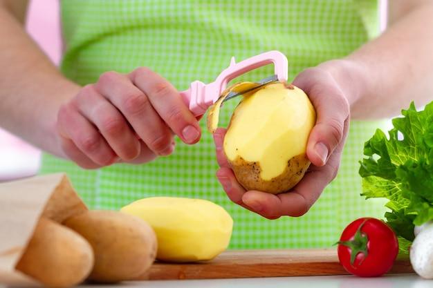 Descascando a batata madura usando um descascador para cozinhar pratos de legumes frescos na cozinha em casa.