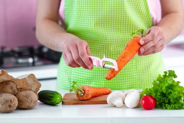 Descascando a cenoura madura com um descascador para cozinhar saladas e pratos de legumes frescos.