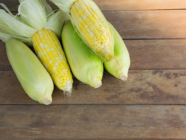 Descascar e descascar o milho cru no fundo da mesa de madeira