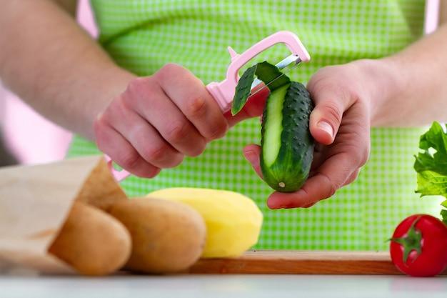 Descascar o pepino com um descascador para cozinhar pratos frescos e saladas de legumes em casa.