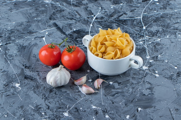 Descasque o macarrão cru em uma tigela com tomates vermelhos frescos e alho.