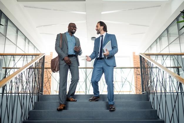 Descendo as escadas. dois prósperos empresários de sucesso descendo as escadas durante o intervalo para o almoço