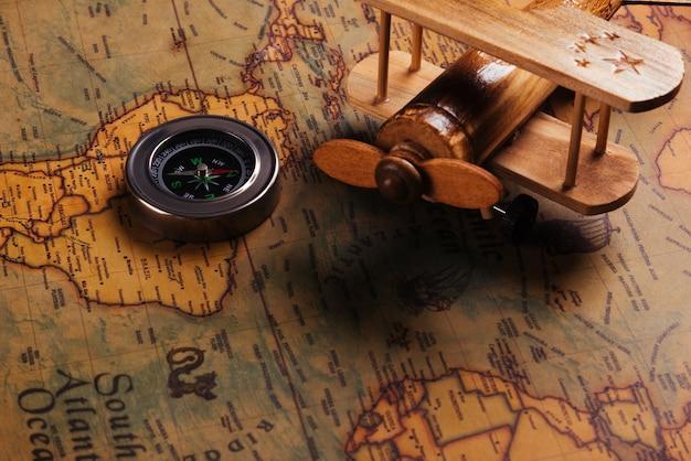 Descoberta da bússola e avião de madeira no mapa-múndi antigo de papel vintage