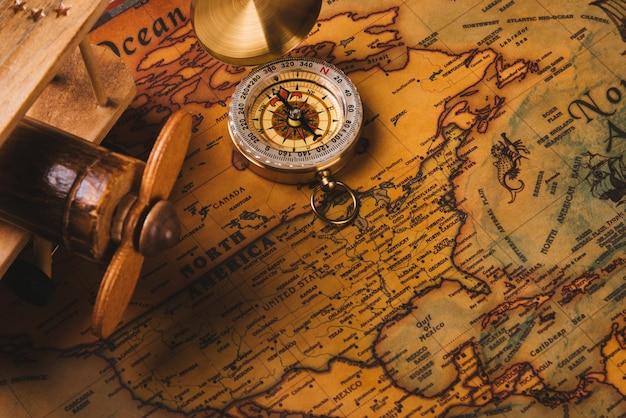 Descoberta de uma bússola antiga e um avião de madeira em um mapa-múndi antigo de papel vintage