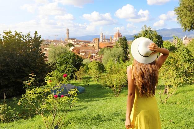Descobrindo florença. vista traseira da jovem turista olhando a paisagem urbana de florença entre as árvores. turismo na toscana.