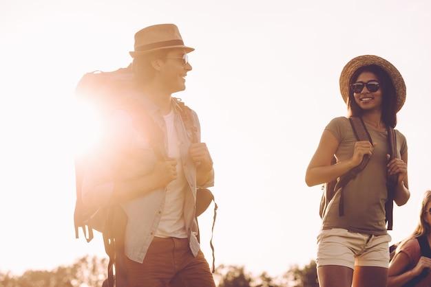 Descobrindo novos lugares juntos. lindo casal jovem com mochilas caminhando juntos e olhando um para o outro com sorrisos