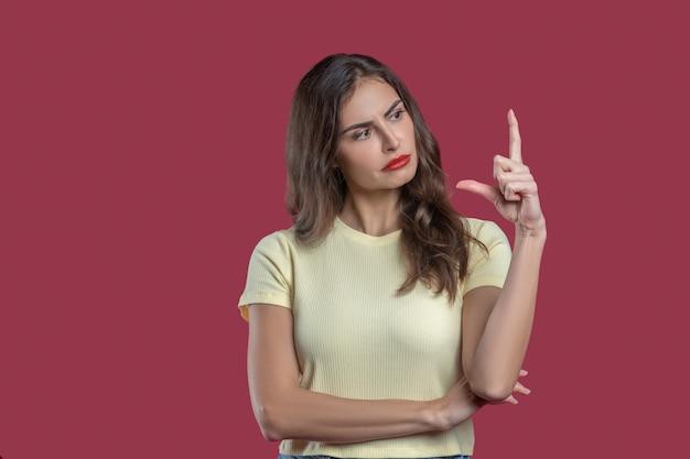 Desconfiança. jovem mulher brilhante de cabelos compridos com rosto sério olhando incrédula para os dedos mostrando distância