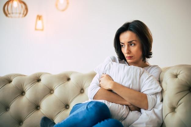 Desconforto. linda mulher triste está sentada em um sofá, abraçando um travesseiro e olhando para o lado, enquanto se sente mal.