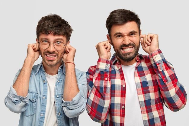 Descontentamento dois caras elegantes tapam os ouvidos com desagrado, cerram os dentes, ignore o barulho alto