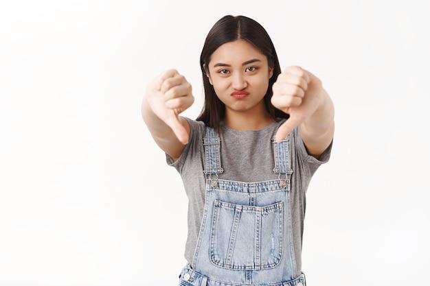 Descontente temperamental ignorante menina morena asiática expressar desaprovação não gosto carrancudo amuado chateado mostrar polegares para baixo taxa filme desinteressante horrível suporte parede branca