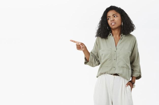Descontente triste mulher de pele escura sentindo ciúme e inveja apontando com pesar e tristeza esquerda