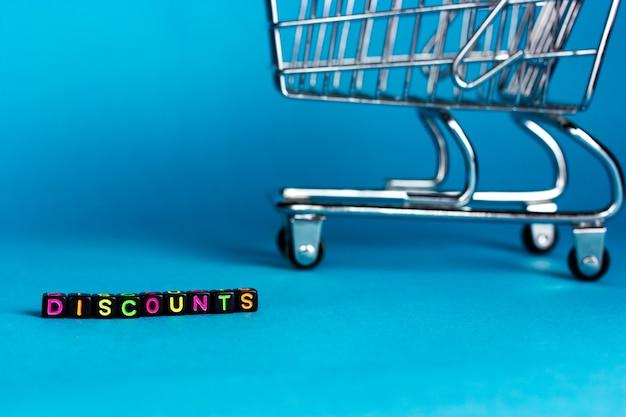 Desconto de letras e carrinho de compras em um fundo azul