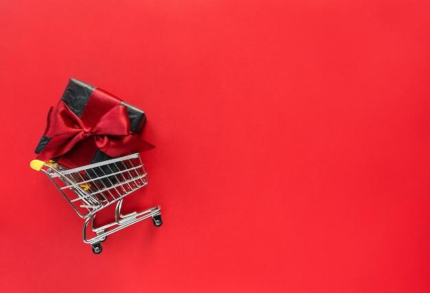 Desconto em vendas de sexta-feira preta, caixa de presente preta em mini carrinho de compras em fundo vermelho com espaço de cópia