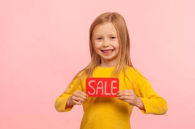 Descontos de férias. animada encantadora menina feliz segurando a inscrição de venda e sorrindo para a câmera, anunciando preços baixos na loja infantil, black friday. foto de estúdio interno isolada em fundo rosa