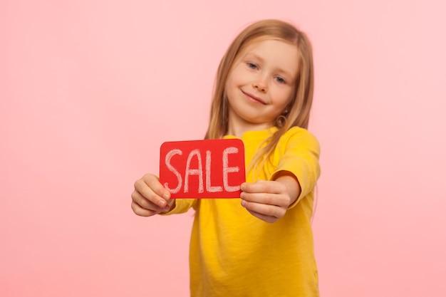 Descontos de fim de semana. animada fofa feliz garotinha mostrando a inscrição de venda e sorrindo para a câmera, anunciando preços baixos na loja infantil, black friday. foto de estúdio interno isolada em fundo rosa