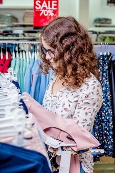 Descontos na loja de moda. a menina escolhe um vestido na loja