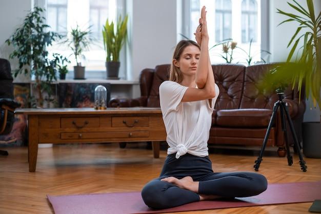 Descontraída jovem desportista vestida com roupas esportivas poses na câmera, fazendo exercícios físicos na sala de estar com móveis modernos.