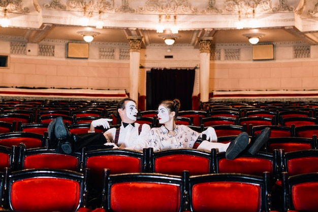 Descontraído feminino e masculino mime sentado na poltrona no auditório