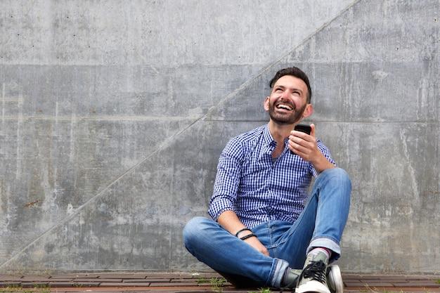 Descontraído homem envelhecido médio sentado contra uma parede