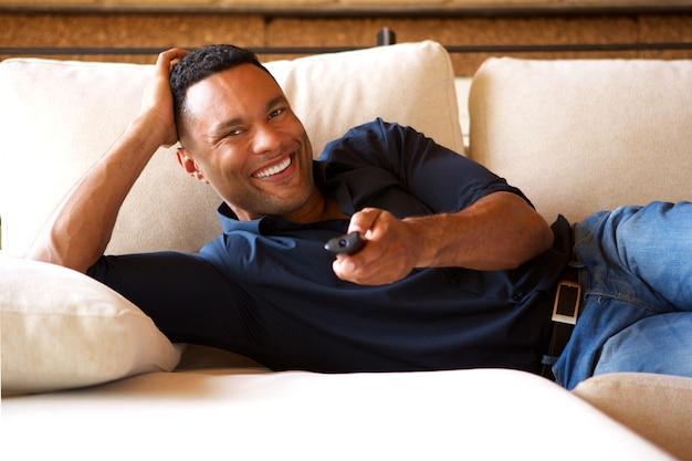 Descontraído jovem negro assistindo tv em casa
