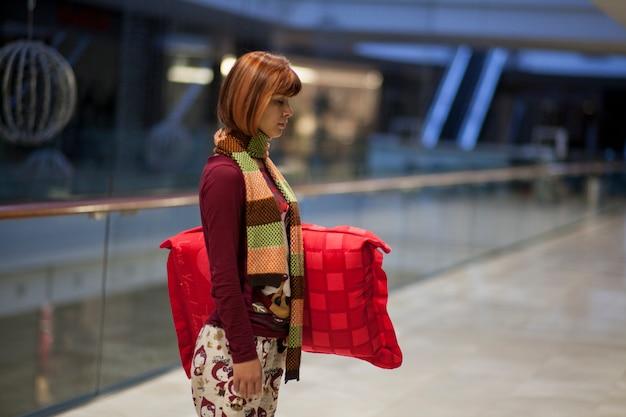 Descontraído mulher segurando uma almofada vermelha