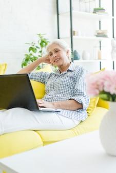 Descontraído sênior mulher sentada no sofá olhando para laptop