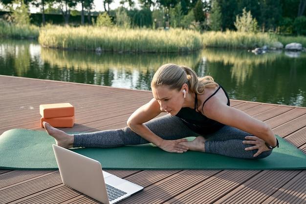 Descubra ioga esportiva atraente mulher de meia-idade assistindo a um tutorial em um laptop enquanto pratica ioga
