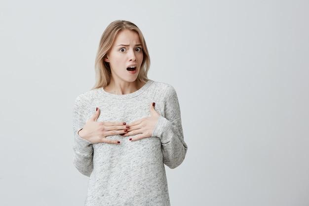 Desculpe? fêmea jovem ofendida perplexa, com cabelos tingidos loiros, apontando para si mesma com as mãos, sentindo-se confusa